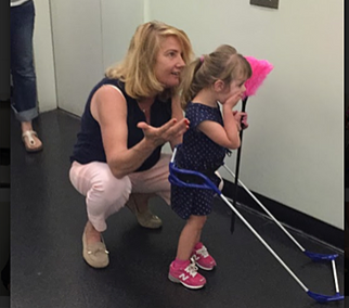 Dr. Ambrose-Zaken croches behind a 3-year-old girl with CVI as she looks surprised at something in front of her- she is wearing her belt cane holding a pink feather duster