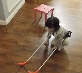 Two year old girl, blind wearing her belt cane seen in crouched position beginning to stand up.
