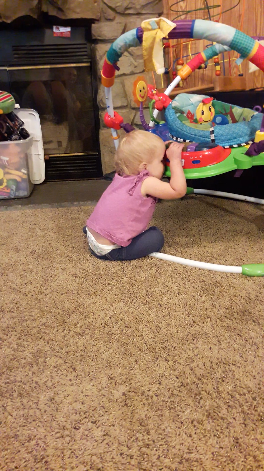 15-month-old girl sits with her mouth connected to the plastic standing baby toy