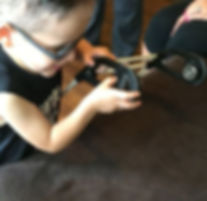 Two year old with tunnel vision is holding a belt cane frame with one hand and probing the magnets with heother, he is string intently athis actions.
