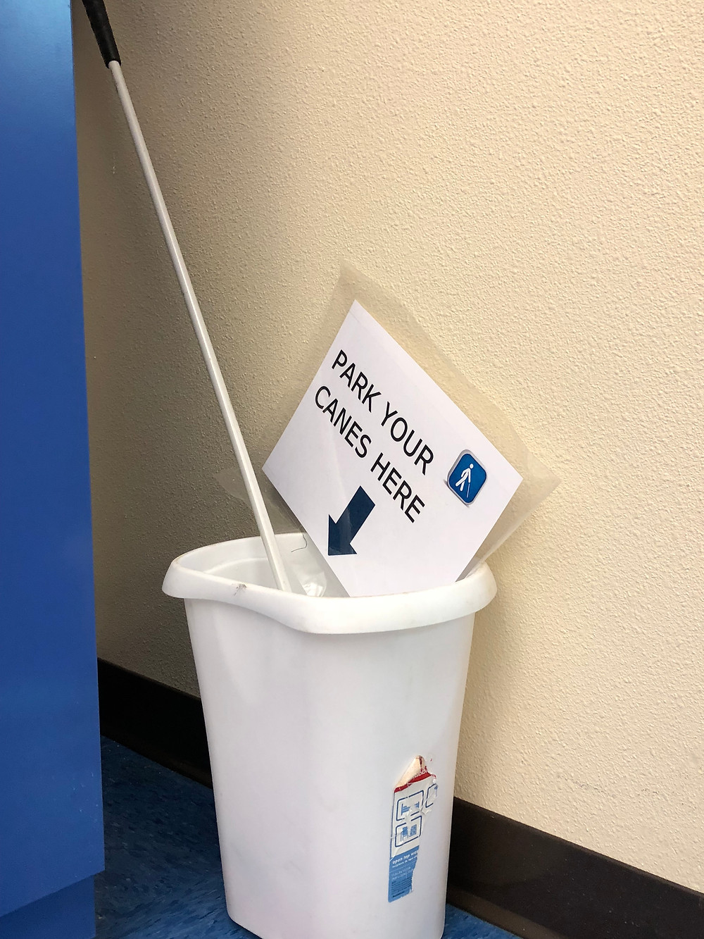 A white trash can holds a white cane. A sign reads park your canes here.