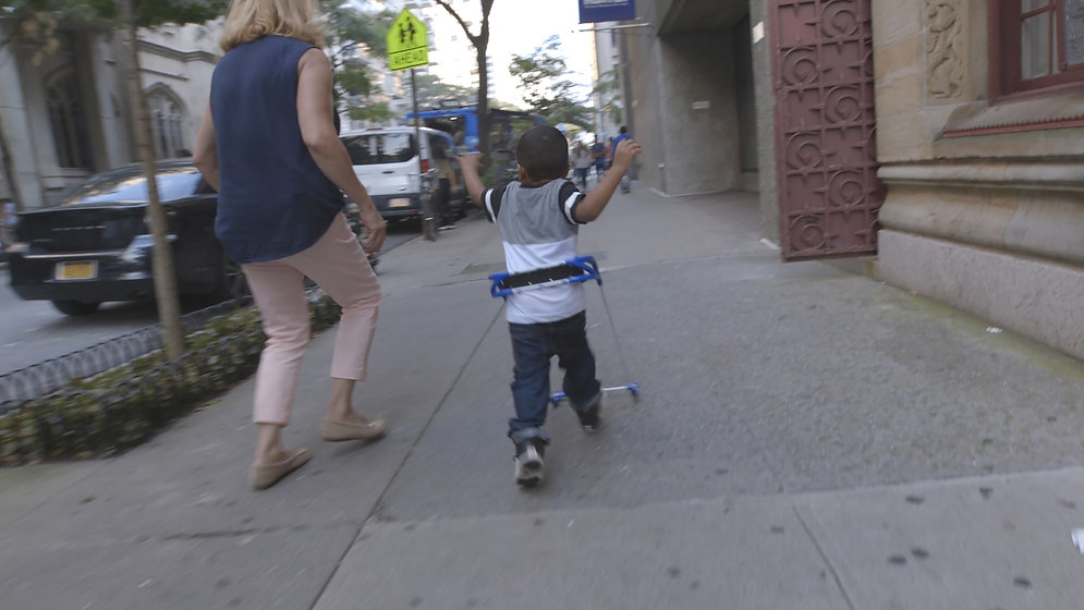 4-year-old boy visually impaired wearing belt cane running down the sidewalk next to Grace Ambrose-Zaken