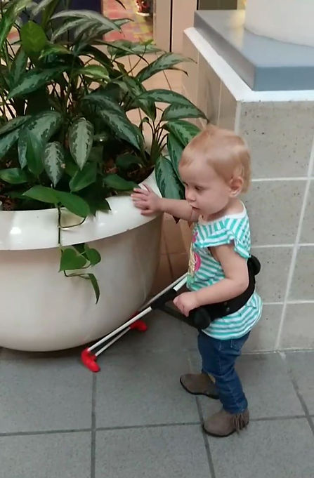 One-year-old has one hand on belt cane the other reaching out to touh potted plant