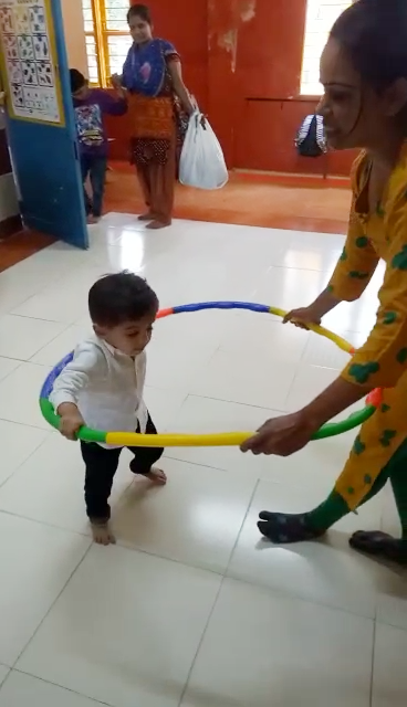 three year old boy in middle of multi-colored circle, his arms on either side, a teacher outside the circle walks backwards pulling him forwards.