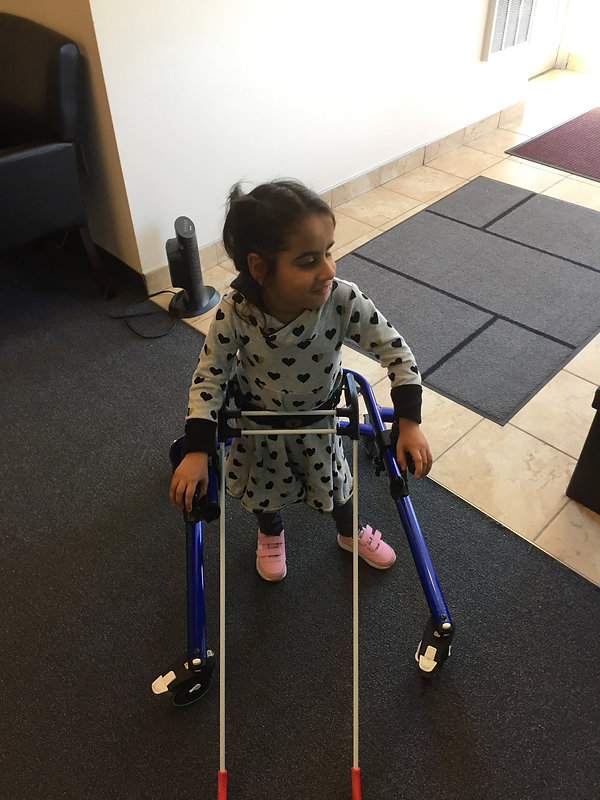 four-year-old girl is standing with cane and rear walker