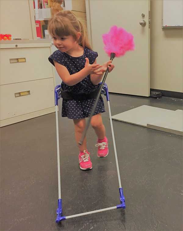 three-year-old girl with CVI walking with belt cane hodling pink duster