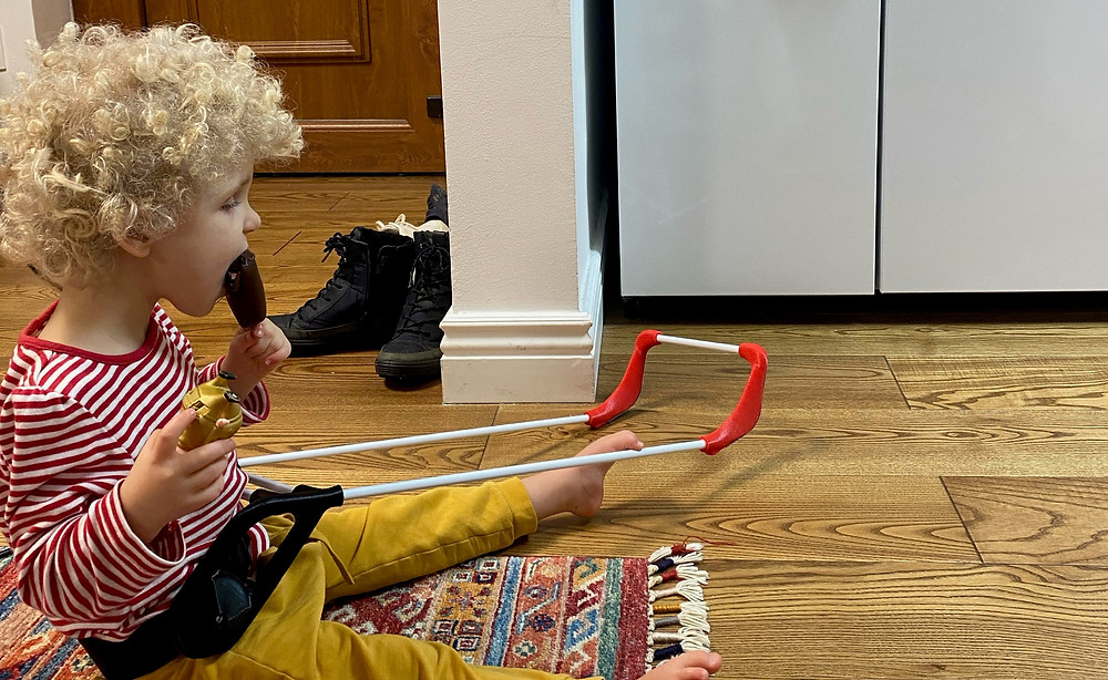 three year old girl sitting on the floor eating a chocolate ice cream pop. Wearing her belt cane her left two is hooked over the top of the cane frame.