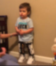 Jaxons, boy, caucasian, brown, t-shirt, has velcro braces on his legs, whte tennis shoes standing against a bown wall