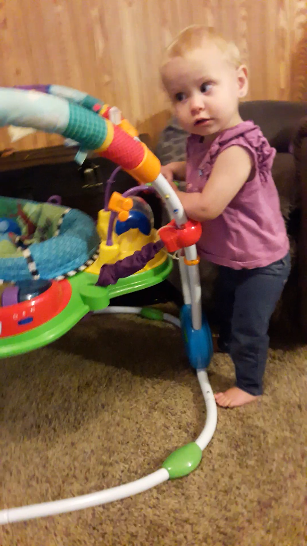 15-month-old girl stands with two hands holding onto a baby toy