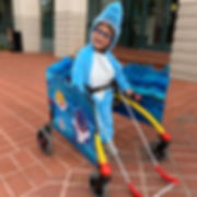 Holt wears a shark costume. He is the blue shark from movie Finding Nemo. His rear walker has blue ocean fabric and he is smiling and wearing his belt cane