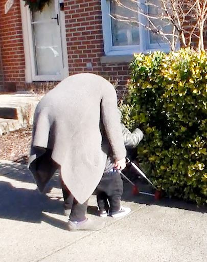 Student M. reaches his hand ahead to locate the bush his cane frame has pushed into.