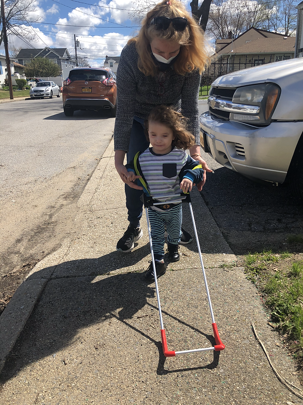 three year old boy with visually impaired due to fetal alcohol syndrome walks wearing his pediatric belt cane assisted from behind by Dr. Grace Ambrose-Zaken