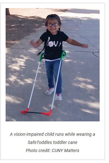 three-year-old girl visually impaired wearing belt cane is running and smiling her shirt reads Love