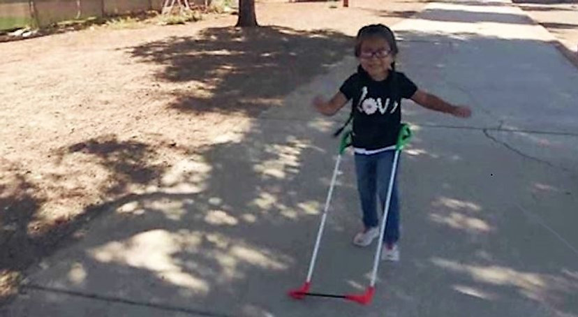 three-year-old girl with visual impairment wearing belt cane is running down sidewalk