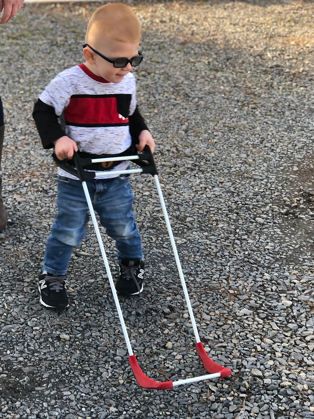 three year old boy walks on packed gravel wearing belt cane, one hand on either grip. Smiles.