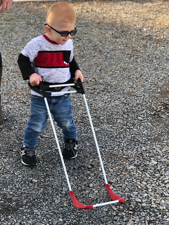three-year-old boy wearing dark glasses due to his cortical visual impairment holds the handles of his pediatric belt cane that extends in front of him on a gravel road.