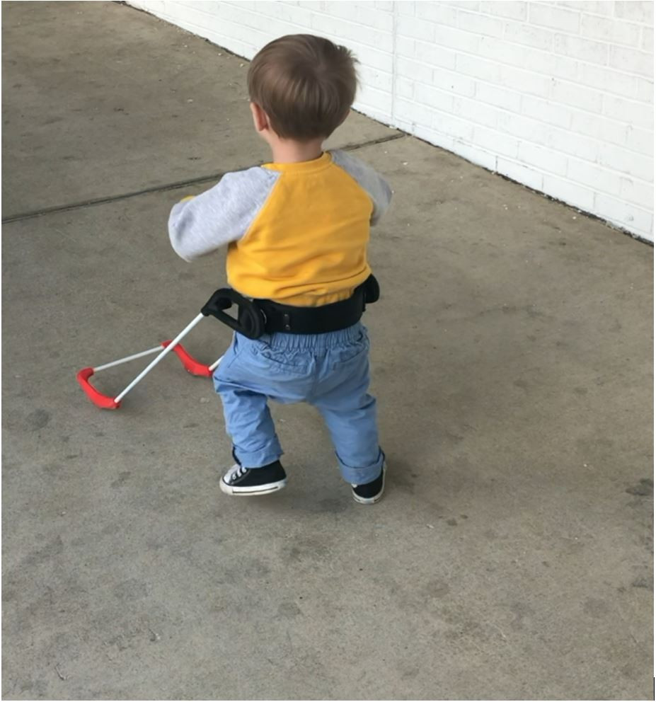 Three-year-old boy walking away from camera wearing belt cane