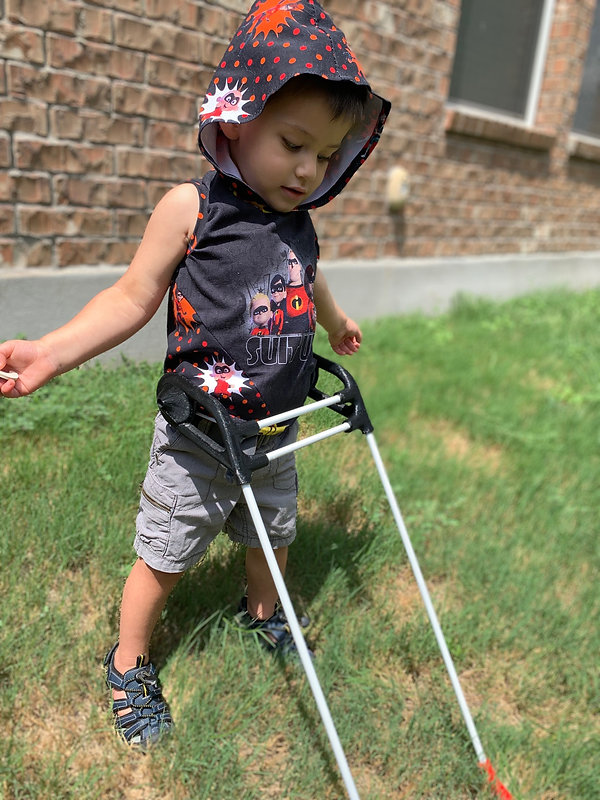 three year old boy stands tall in grass wearing belt cane