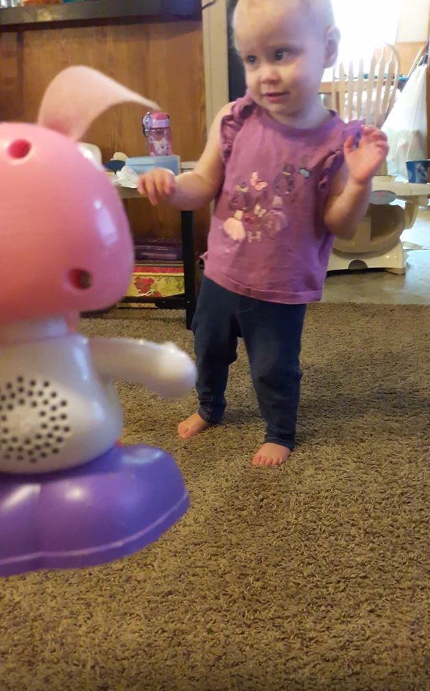 One year old girl, hands up, leaning to left, mid-step has no mobility tool.