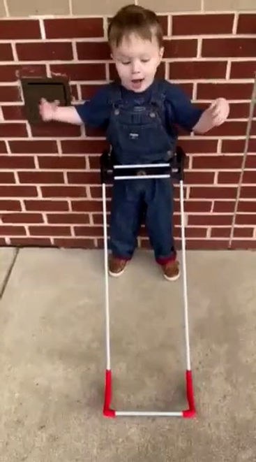 three year old boy with Septo Optic Dysplasia has light perception seen standing by a brick wall, happy wearing his pediatric belt cane