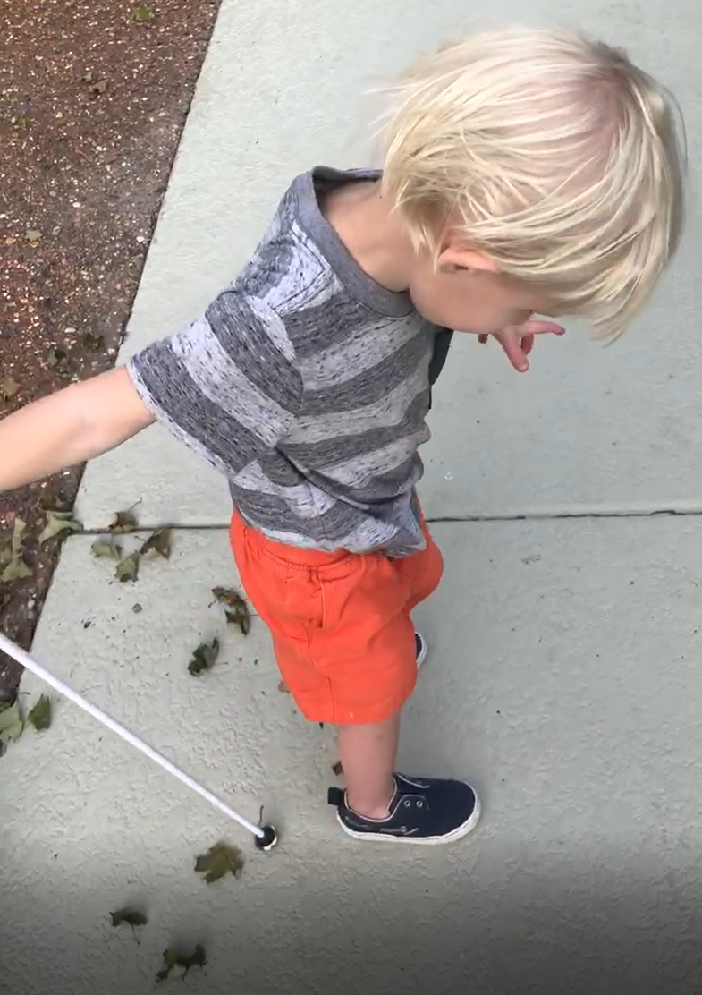 Three year old holds white cane behind him.