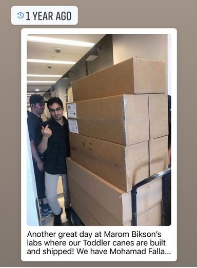 Mohamad stands next to 8 shipping boxes stacked on a mail cart. title reads 1 year ago, below says aonther great day at Marom Bikson's labs where our Toddler Canes are built and shipped! Weh have Mohamad Falla...