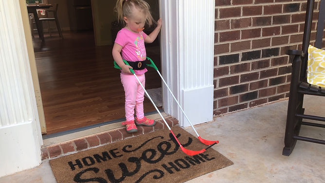two-year-old stands on mat wearing her belt cane, mat that reads home sweet home