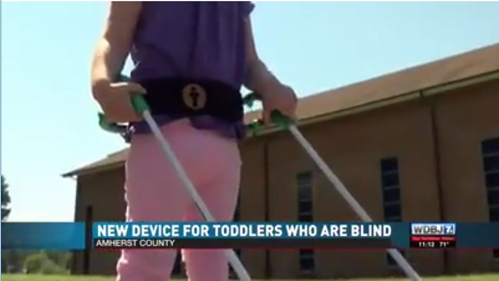 WDBJ 7 screenshot lined up with the above picture so that the top is the girl's head, this is the girl's body with the belt cane. New Device For Toddlers Who Are Blind Amherst County