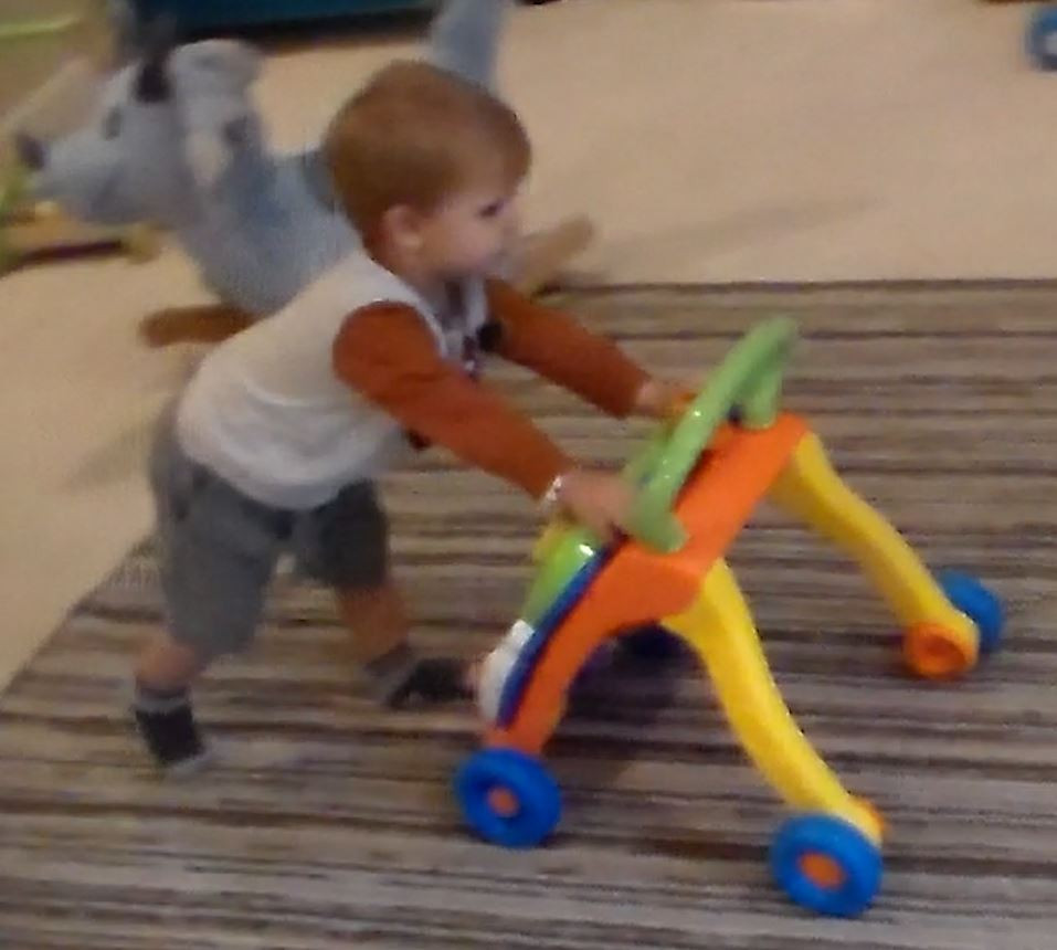 Matias leans over to push his colorful push toy across the room