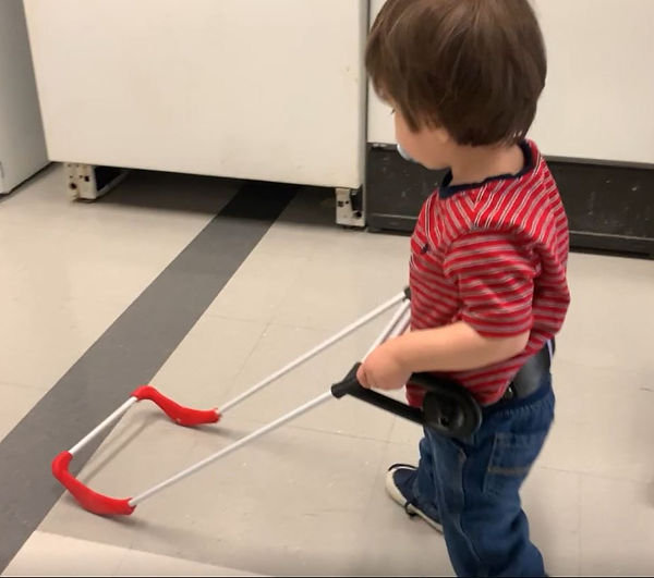 one-year-old boy who is blind is seen from the side view. He is walking down a university hallway wearing his pediatric belt cane, his hands grip the handle and he has a binkie in his mouth.