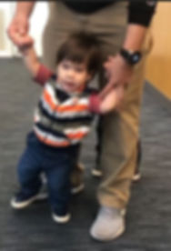 Maddox, boy, hispanic, black hair,striped vest, blue pants, tennis shoes. Father behind him holds each hand in his.