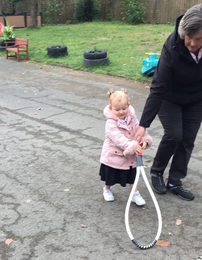three year old girl holds on to top of tear shaped (oversized tennis racket-looks like) and her teacher holds it too- to help position.