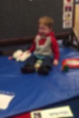 Marshall, caucasian, bonde, sits on gym mat, sweat shirt, jeans, tennis shoes