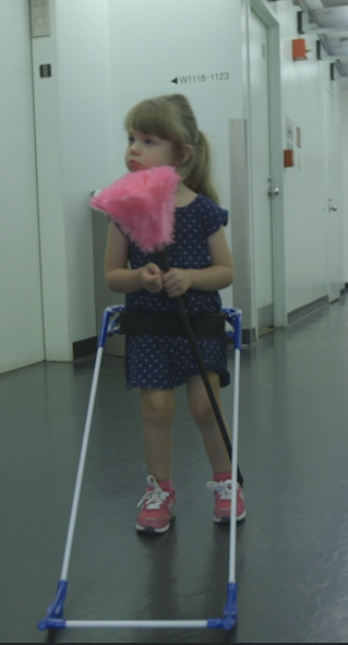 three-year-old girl with CVI wearing belt cane holding pink feather duster.