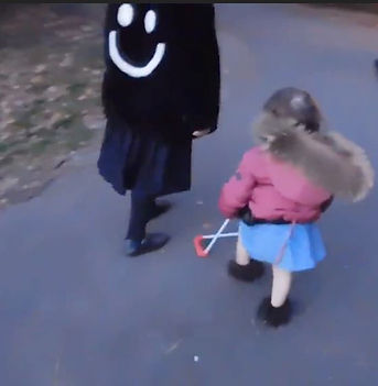 Two people seen walking side-by-side, one blind two-year-old girl is wearing a belt cane, the other has a smily face on the back of her jacket.