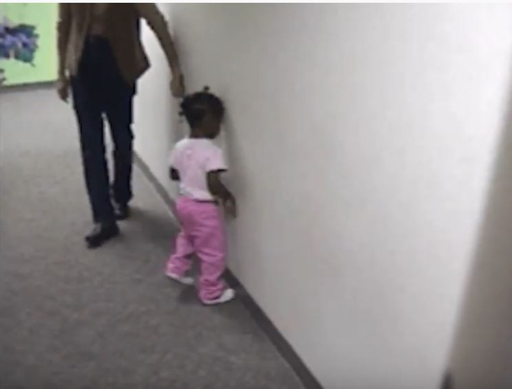 A three-year-old girl dressed in pink is seen colliding with a wall.
