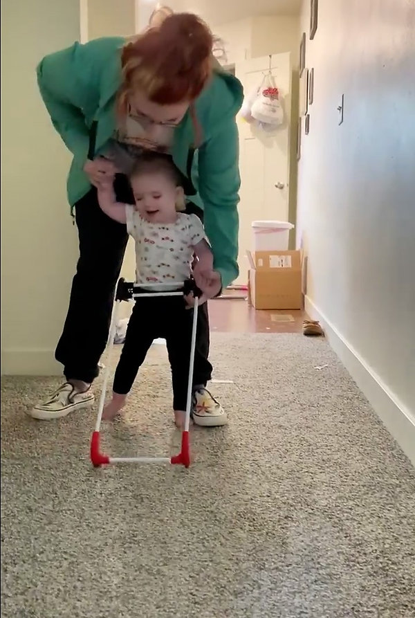 one year old girl visually impaired due to Mainzer-Salindinio syndrome wears her pediatric belt cane at home walks with assistance from behind by her mom