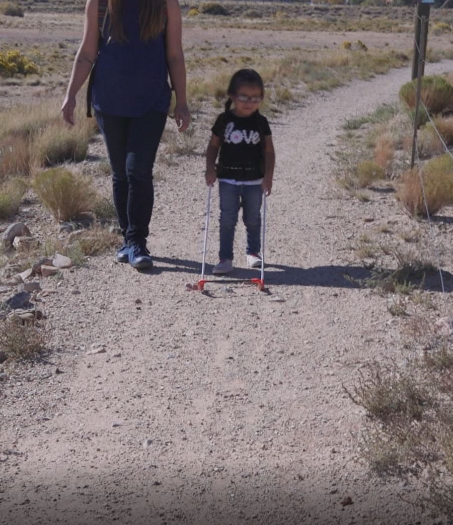 Audrina is walking on a gravel path, wearing her belt cane. the base of the frame is two steps ahead and in front of her feet providing safe mobility.