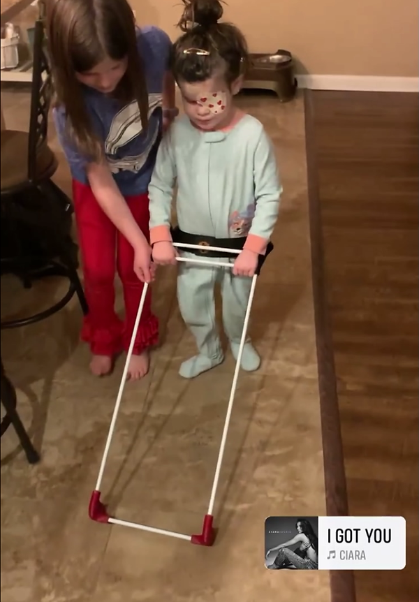 three year old girl is blind - microthamia walking wearing her pediatric belt cane, her sister seen providing assistance.