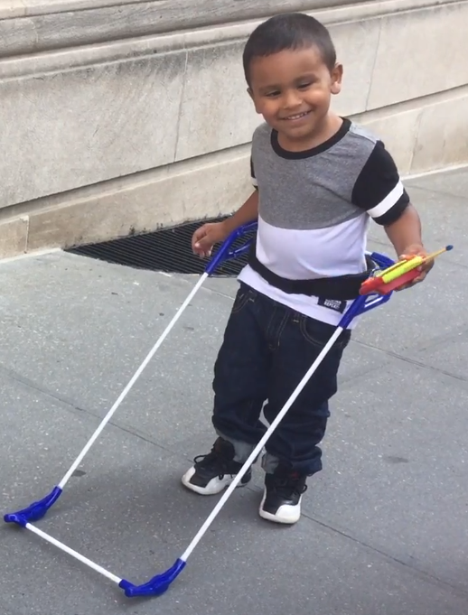 4-year-old stands on sidewalk wearing his belt cane smiling