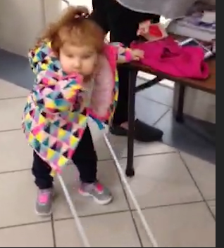 two year old stands wearing her belt cane one hand in mouth the other resting on a table