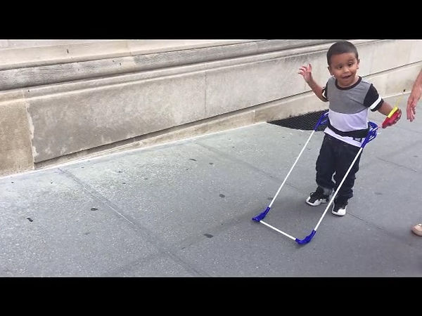 four-year-old boy very happy playing on sidewalk wearing his belt cane