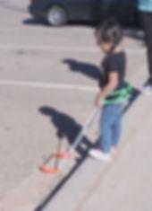 three year old girl walking wearing belt cane.