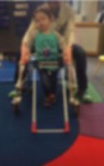 Three year old boy walking wearing belt cae and a walker