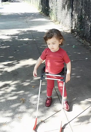 two year old girl who is blind stands happily on a sidewalk, independently walking (not holding a hand) - wearing her belt cane.