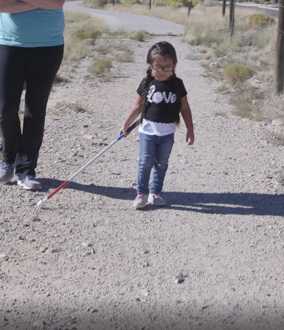 Audrina is walking on gravel path, her rod cane is in her right hand and the cane tip is on the ground far off to her right side.
