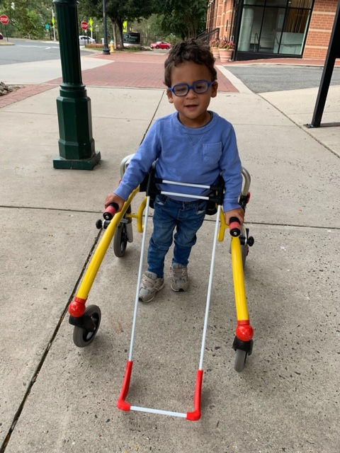 Boy walking wearing his cane on sidewalk and both hands holding the gait trainer used for balance
