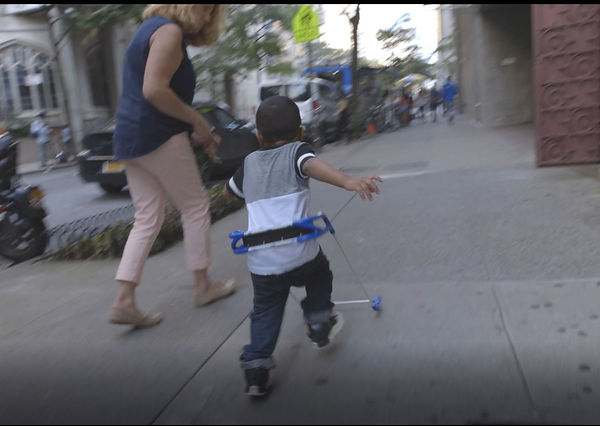 four-year-old boy and Grace Ambrose-Zaken running down 68th street in NYC he is wearing belt cane