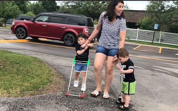 Four-year-old girl wearing belt cane, walks hand in hand with her mom and brother through school parking lot