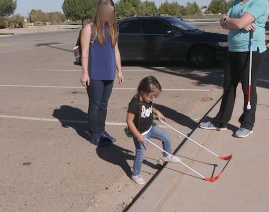 three-year-old girl, visually impaired wearing belt cane steps up on curb, both hands manipulating the cane